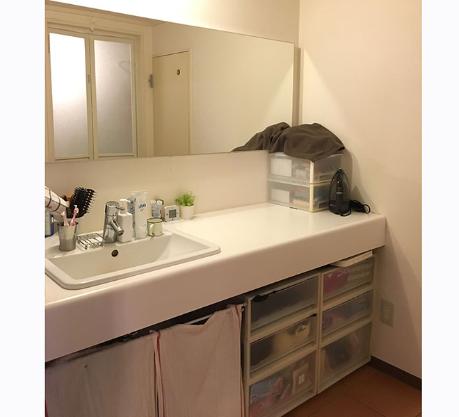 洗面所はコストを抑えるため、シンプルな天板の上に洗面ボウルを設置してもらうだけにとどめた。下部はオープンにして既製品のボックスなどで収納。大きな鏡はNさん自身が購入して取り付けている。
