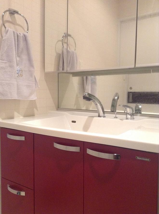 洗面台の収納扉は赤をチョイス。「この家のテーマカラーを赤に決めて、あちこちで取り入れました」とKさん。