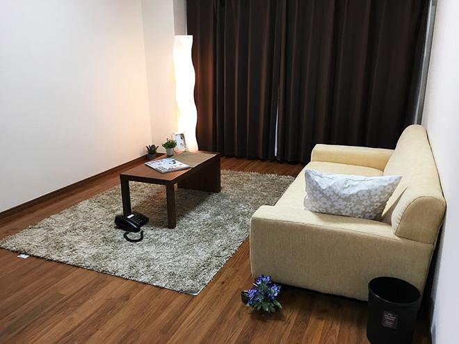 フローリングの床やカーテン、サイドテーブルはダークブラウンで統一され、落ち着いた印象。ソファや置き型の照明が空間のアクセントになっている。