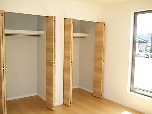 2階洋室の収納には、ハンガーパイプや棚が設置されている。現在は寝室の一つとして活用しているそう。「洋服をしまうべきなのでしょうが、現在は私の漫画が積み上がっている状態。早く読まなければ……(笑)」。