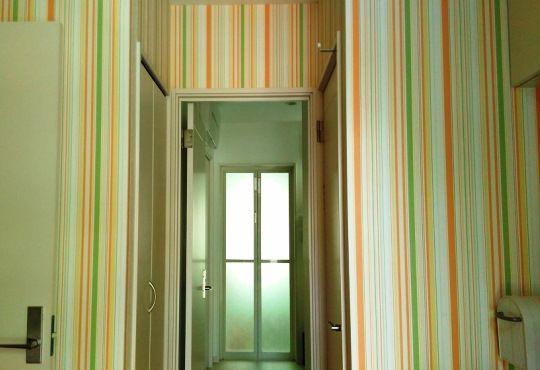 玄関ホールの壁紙はカラフルなストライプをチョイス。「遊びに来たみなさんが、第一声で『可愛い』と言ってくれます」。