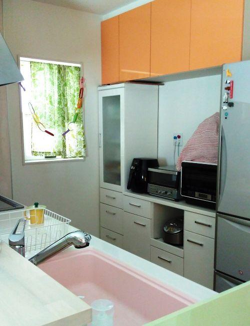 キッチンは側面をグリーン、吊り戸棚をオレンジにして、その場にいるだけで楽しくなる空間に。手前のカウンターは、お皿の一時置きとして活用している。