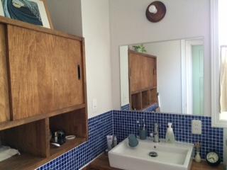 壁にタイルを張るなど、デザインにこだわった洗面所。「タオルや化粧品をしまうため、サイドの壁一面を収納にしてもらいました。タオルをさっと取り出せて便利です」。