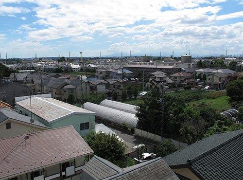 北側にはバス停があり、写真の南側は低層地域。将来的にも高い建物は建たないため、気持ちのいい空が広がっている。「天気のいい日は右手に富士山も見えます」。