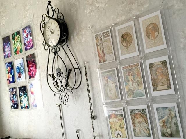 Sさんの居室の壁には、ポストカードや自身で撮影した写真を飾っている。アンティークの時計は、オークションで購入した物。「元々ウエディングフォトなどを手掛けていて、現在も趣味の延長として、音楽関係のイベントやCDの撮影を手掛けています。私も妻もアール・ヌーヴォー様式の絵画が好きで、ポストカードを飾っています」。